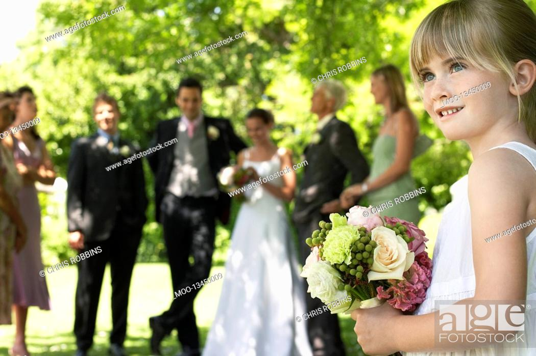 Stock Photo: Young girl holding bouquet bride and groom in background side view.