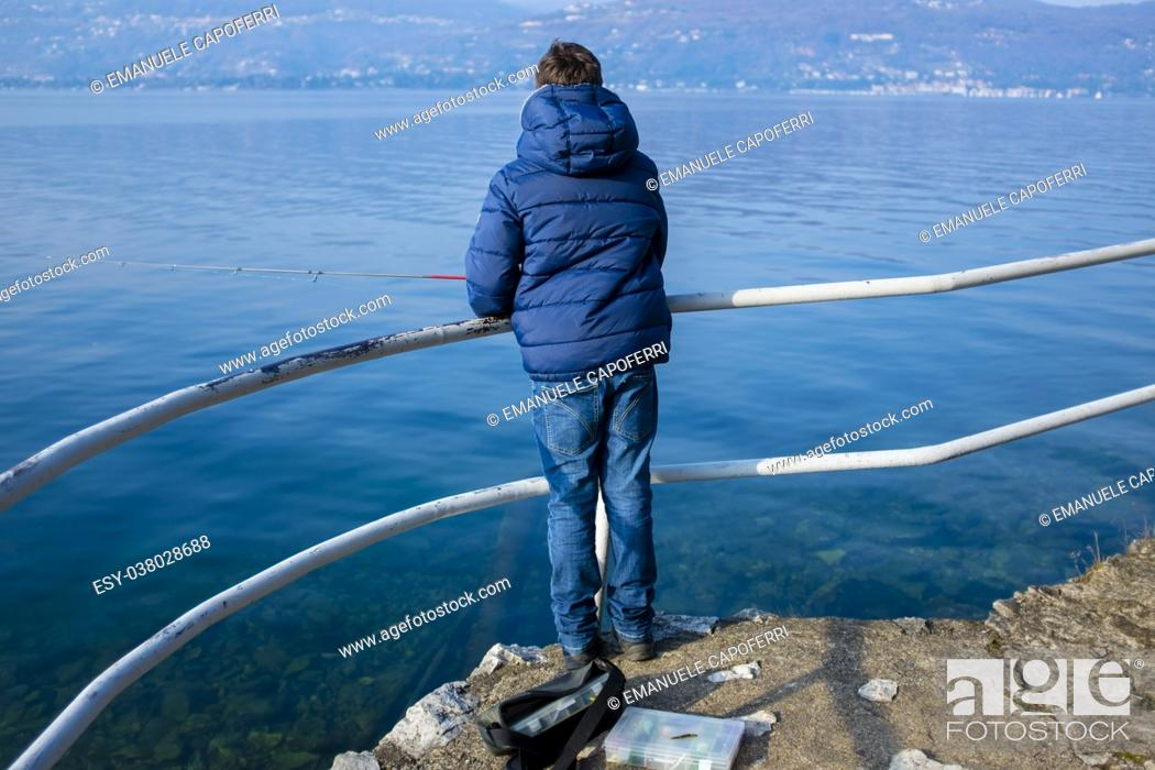 Stock Photo: teenager on the shore of Lake Maggiore are fishing in the winter on a sunny day.