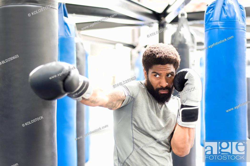 Stock Photo: Portrait of Black man wearing boxing gloves in gymnasium.