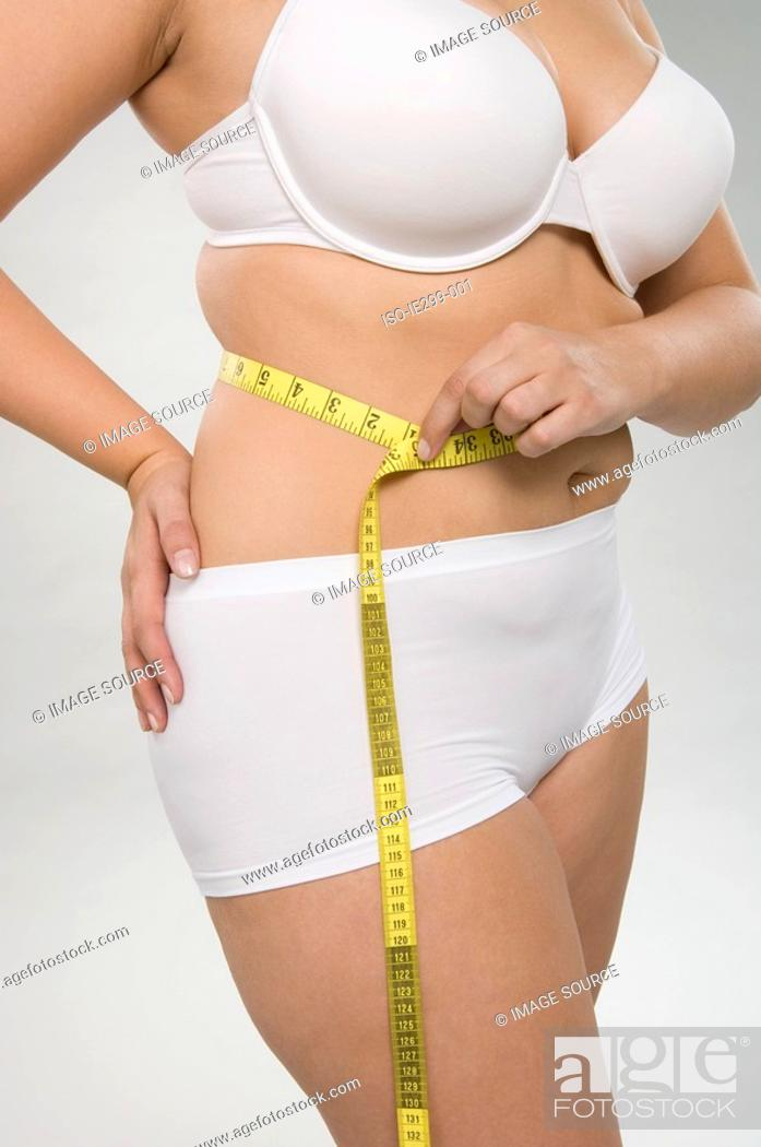 Stock Photo: A woman measuring her waist.