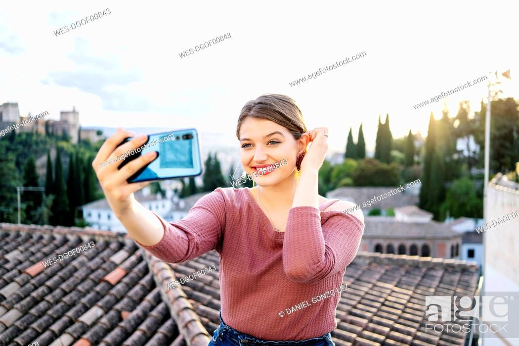 Imagen: Portrait of smiling woman taking a selfie with Alhambra in background, Granada, Spain.