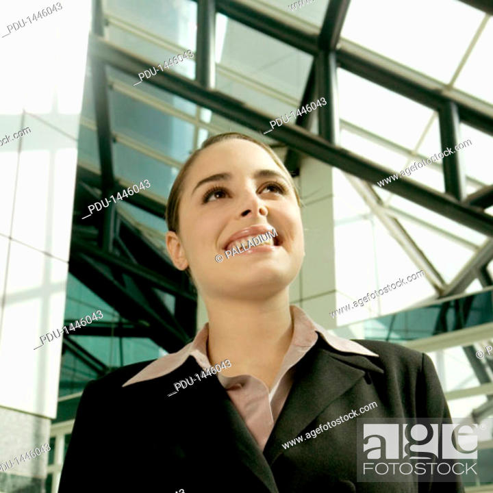 Stock Photo: Smiling businesswoman standing under skylight and looking up.