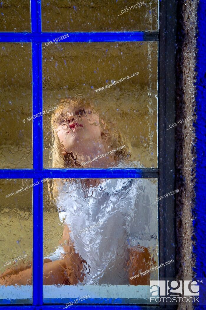 Stock Photo: A five-year-old girl looks out her window on a rainy night in suburban Lake Forest, CA.