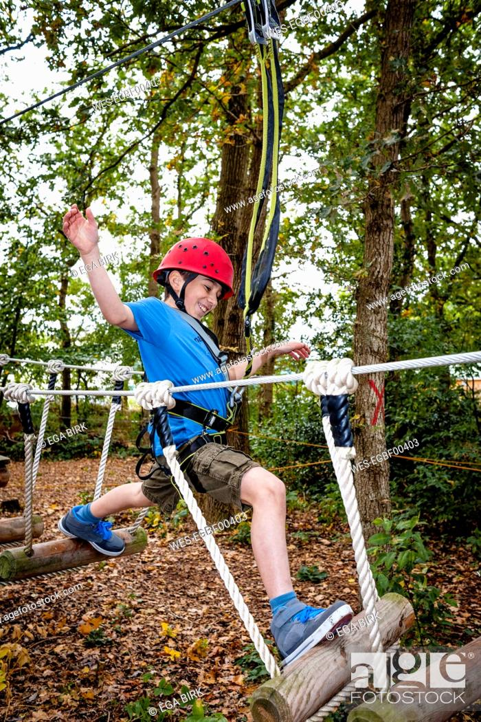 Stock Photo: Boy on a rope course in forest.