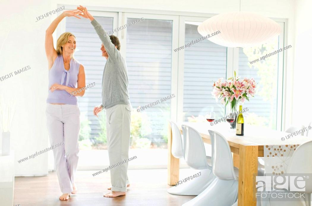 Stock Photo: Couple dancing in dining room.