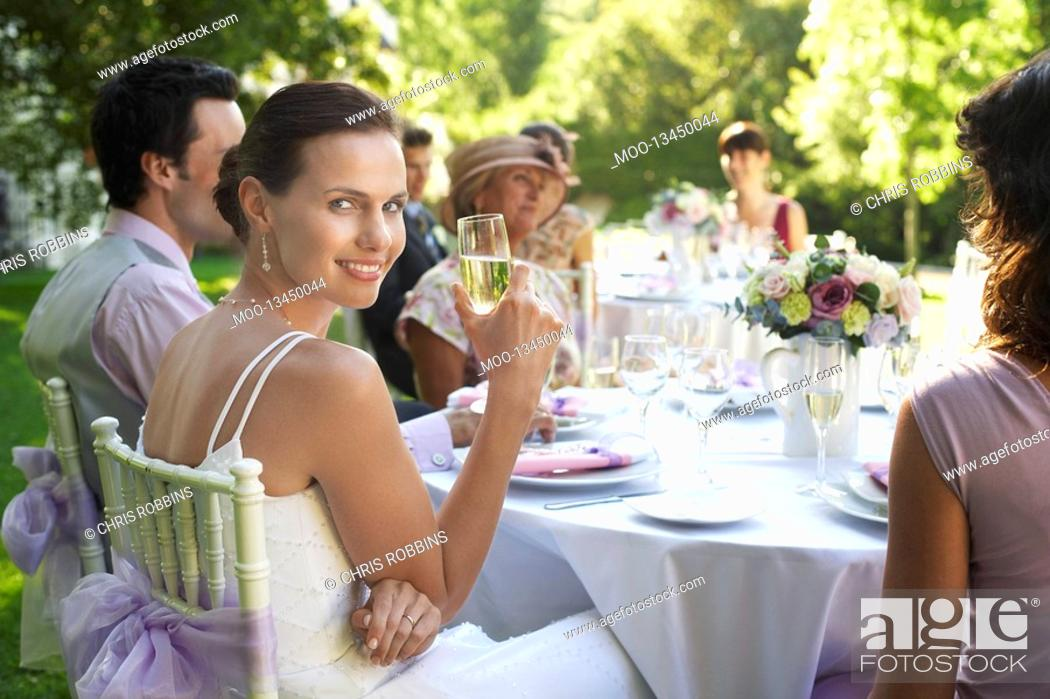 Stock Photo: Bride sitting at wedding table holding wineglass smiling.