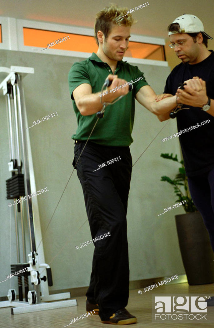 Stock Photo: Young man at the fitness studio, gym, working out, doing exercises, controlled by a coach.