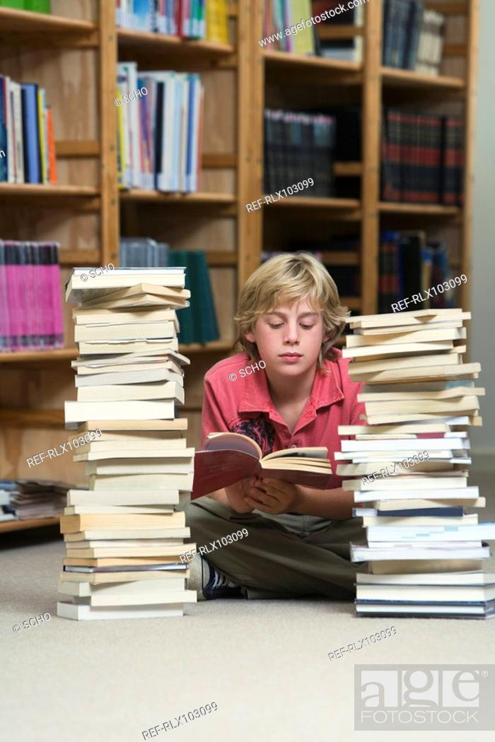 Stock Photo: Boy 10-13 in library, reading and sitting between two piles of school books.