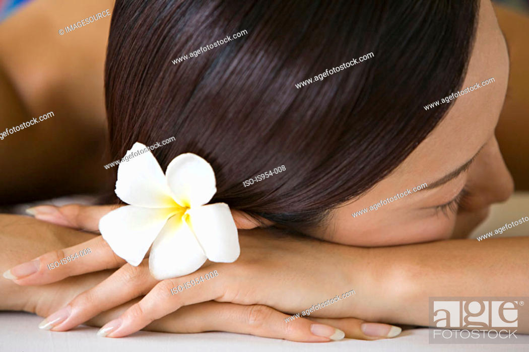Stock Photo: Woman with flower in hair lying down.