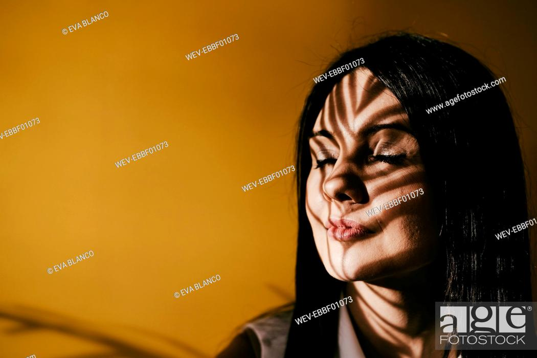 Stock Photo: Mid adult woman with leaf shadow on face against yellow wall.