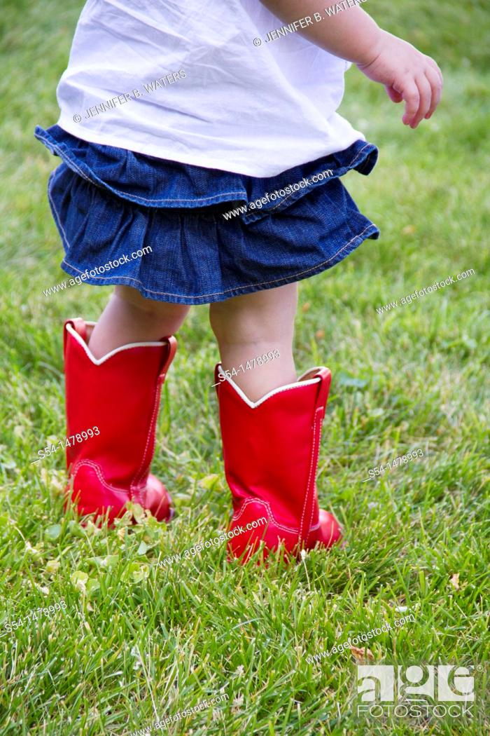 Stock Photo: A toddler standing in a lawn wearing bright red boots.