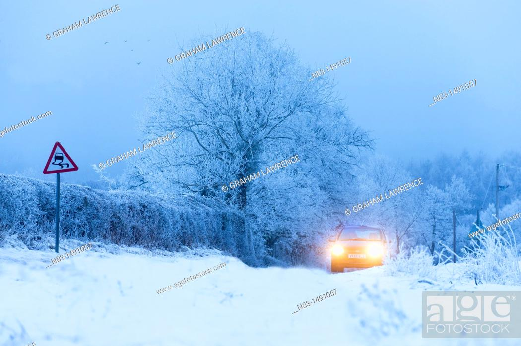 Stock Photo: A car drives through a winter landscape in Powys, Wales, UK.