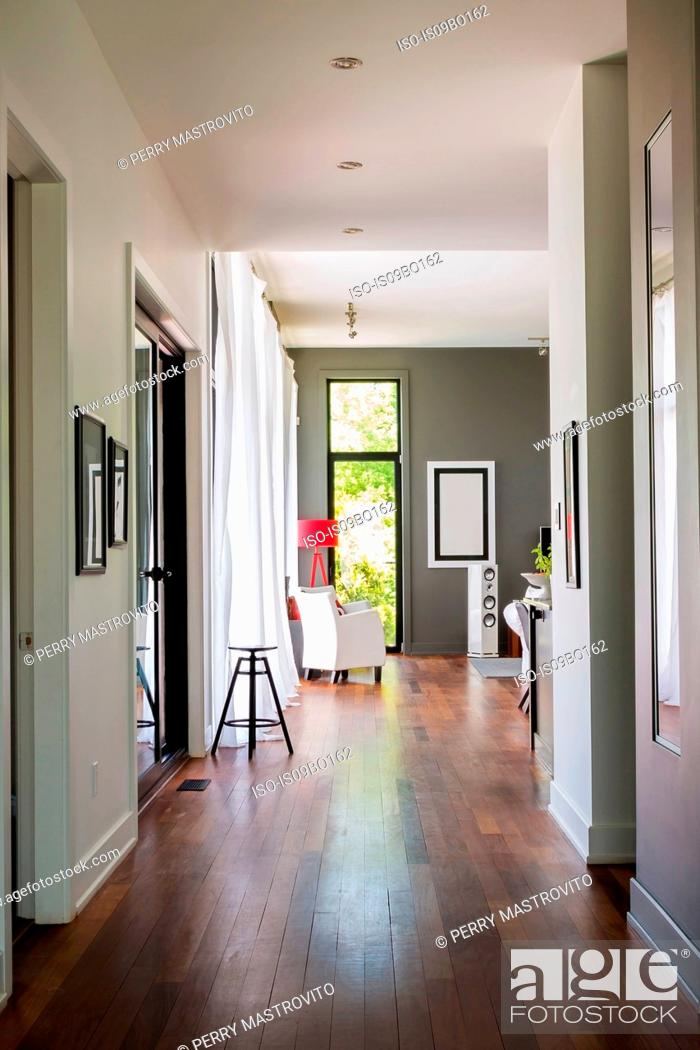 Stock Photo: Hallway with qumaru wood floorboards leading to living room with white leather armchair, luxurious modern cube style house interior.