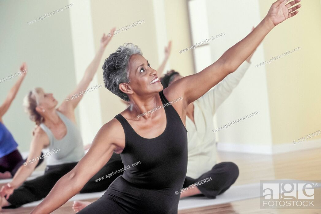 Stock Photo: Older women stretching in yoga class.