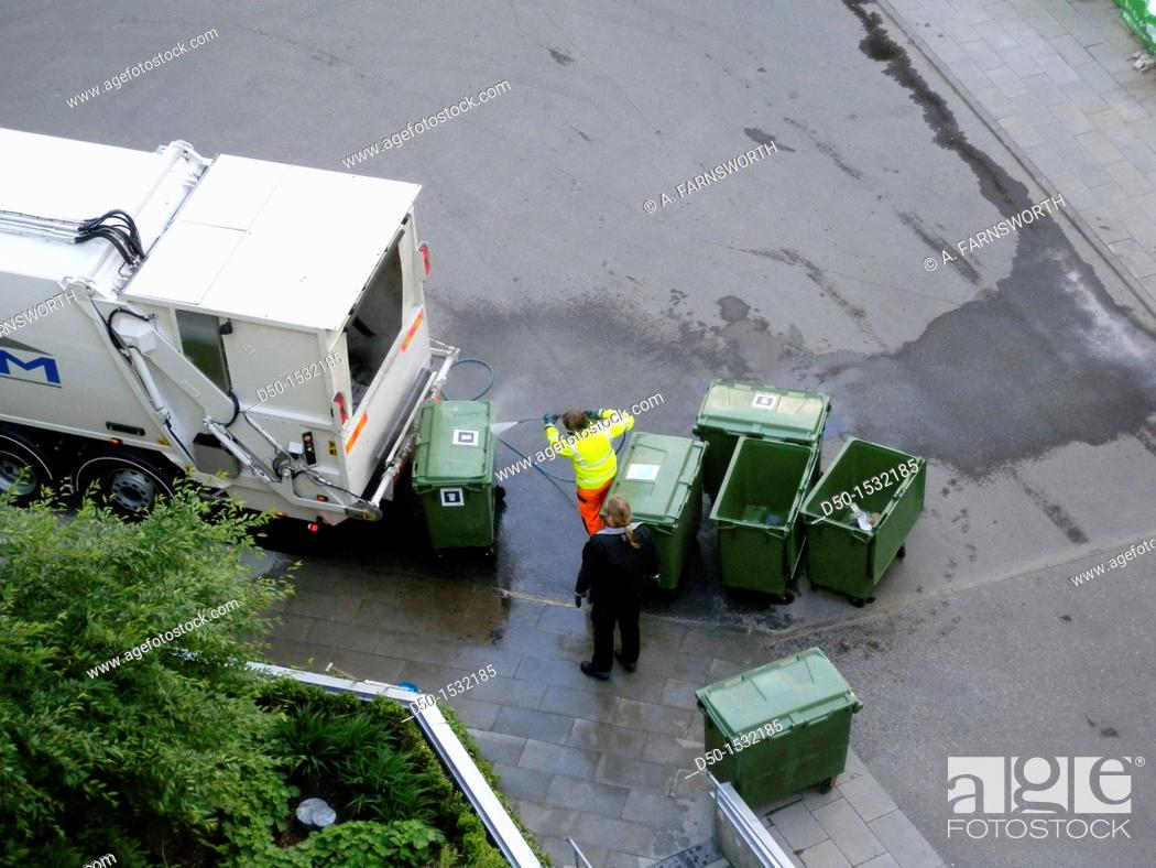 Stock Photo: STOCKHOLM SWEDEN Garbage cans getting pressure cleaned with water at a residential complex.