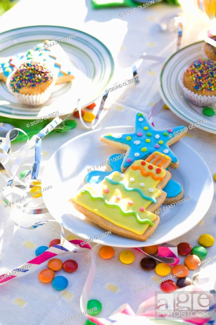 Stock Photo: Iced cookies, cupcakes on table decorated with streamers and candy.