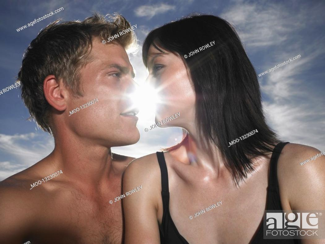 Stock Photo: Couple about to kiss with sun behind outdoors.