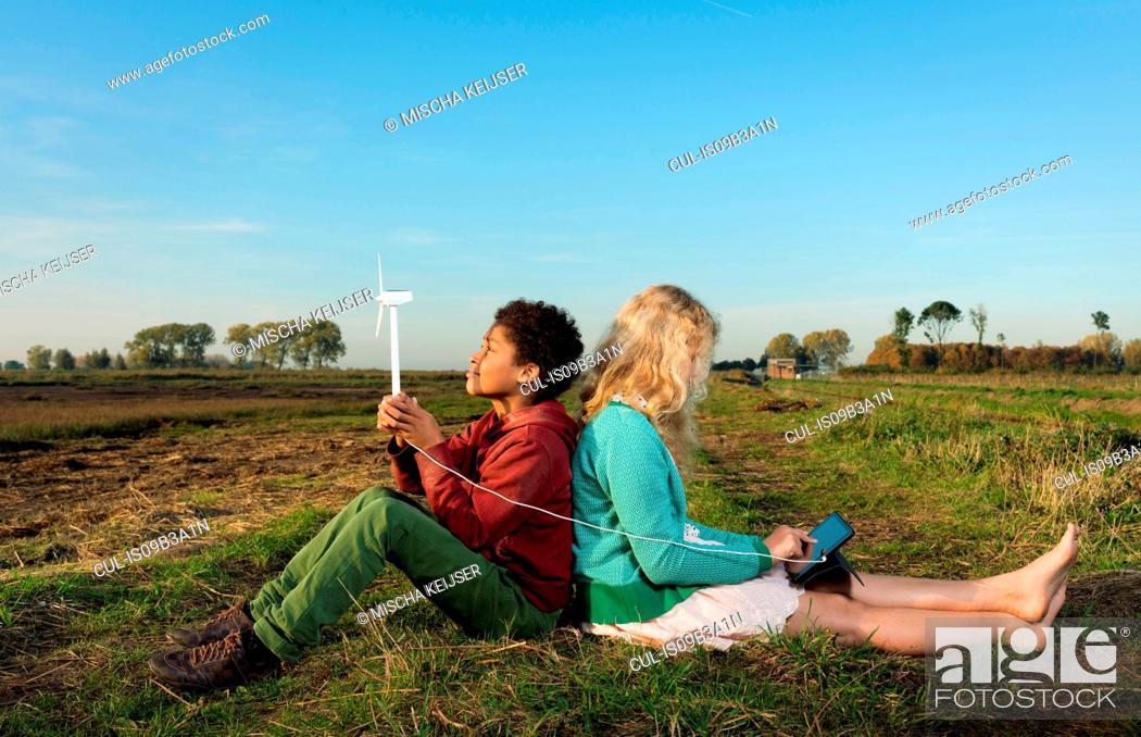 Stock Photo: Children using miniature wind turbine to power digital tablet, Breda, Netherlands.