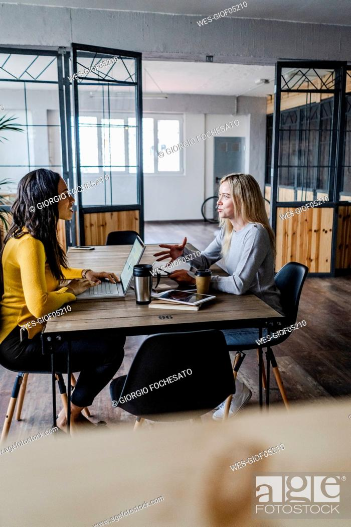 Stock Photo: Two young businesswomen talking at conference table in loft office.