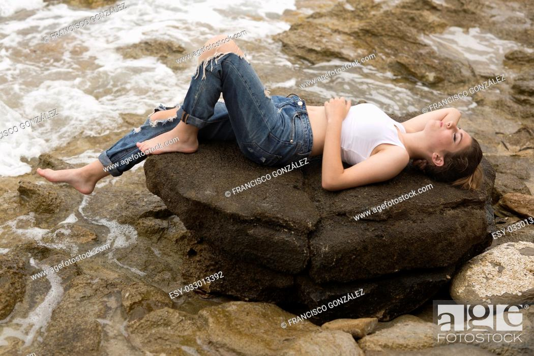 Photo de stock: Teenage girl lying on the rocks of a creek of Villajoyosa, in the province of Alicante, Spain.
