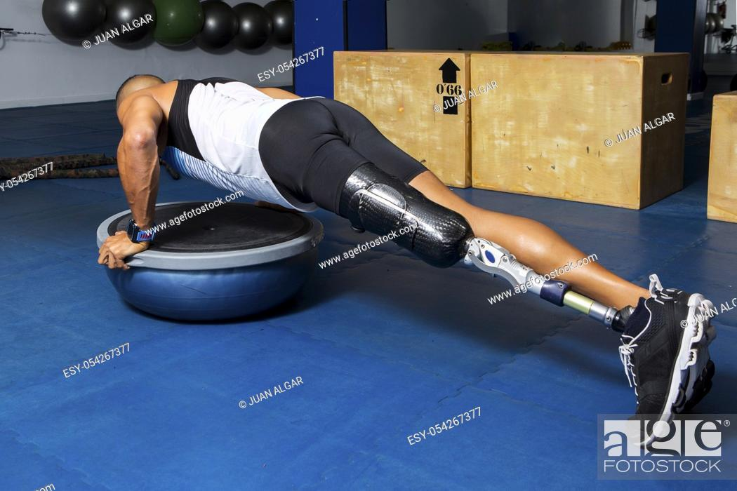 Stock Photo: Side view of sportsman with artificial leg limb training in gym and doing push-ups on bosu ball.