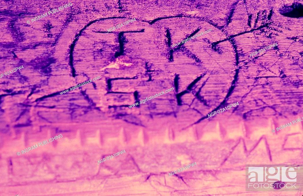 Stock Photo: Initials in a heart etched on wood.