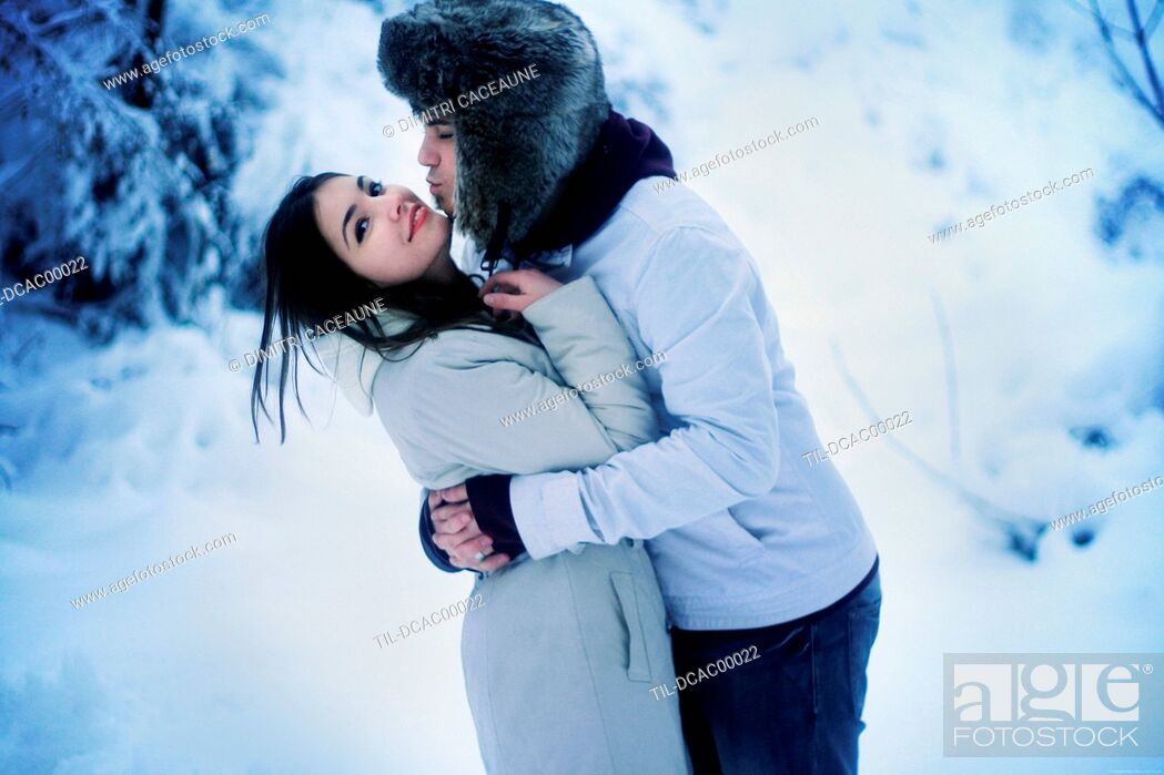 Stock Photo: Young adult couple in winter embrace outdoors in snow.