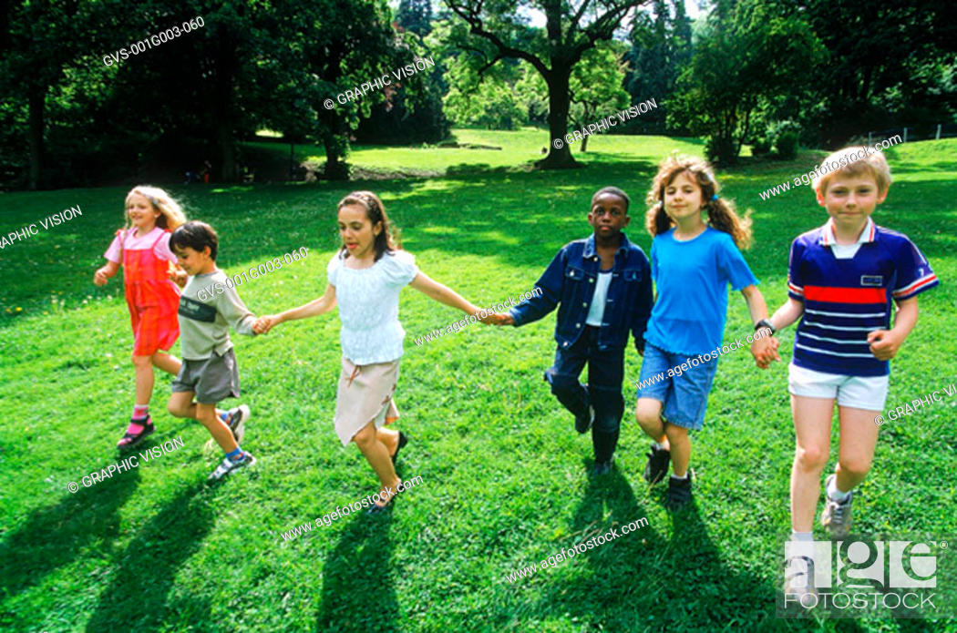 Stock Photo: Young children holding hands running on a lawn.