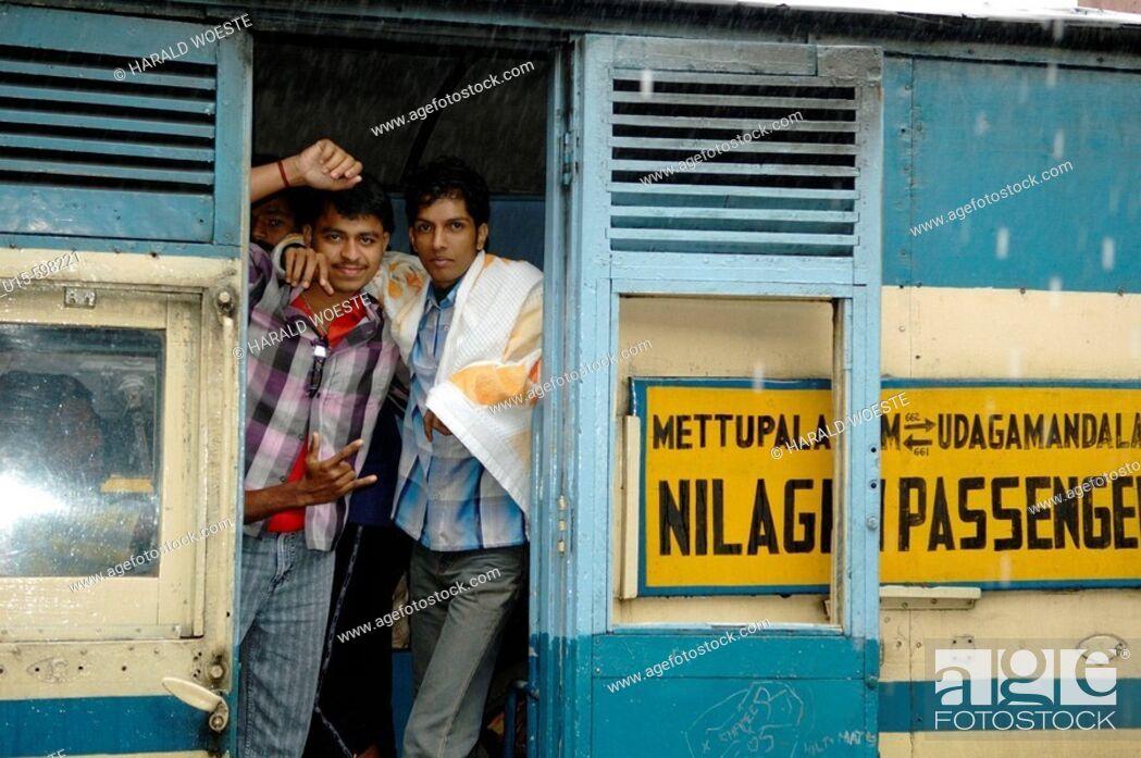Stock Photo: Loughing young indian men on board the Nilgiri Mountain Railway at Coonoor railway station in rain. India, Tamil Nadu, Coonoor 2005.