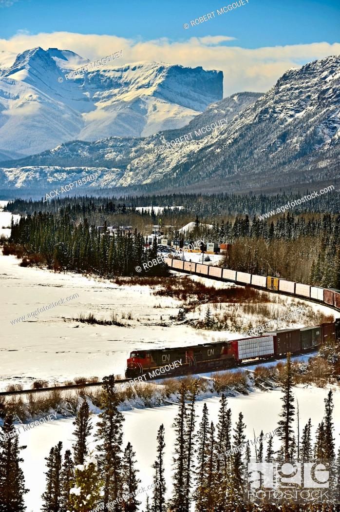 Stock Photo: A Canadian National freight train traveling through the snow - capped rocky mountains of Alberta Canada.