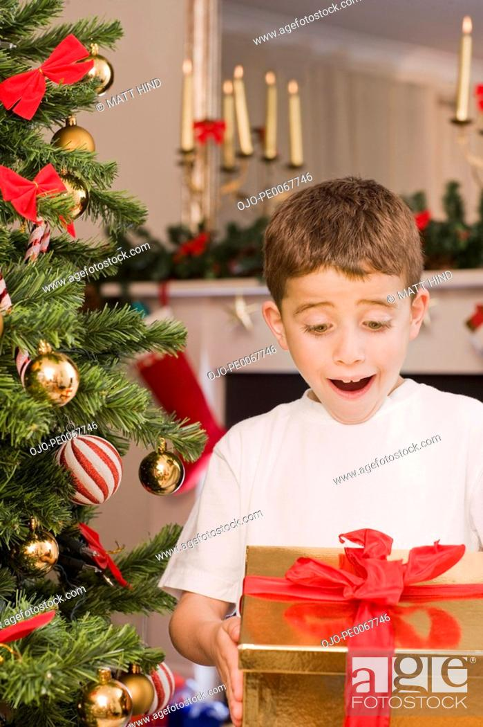 Stock Photo: Surprised boy holding Christmas gift.