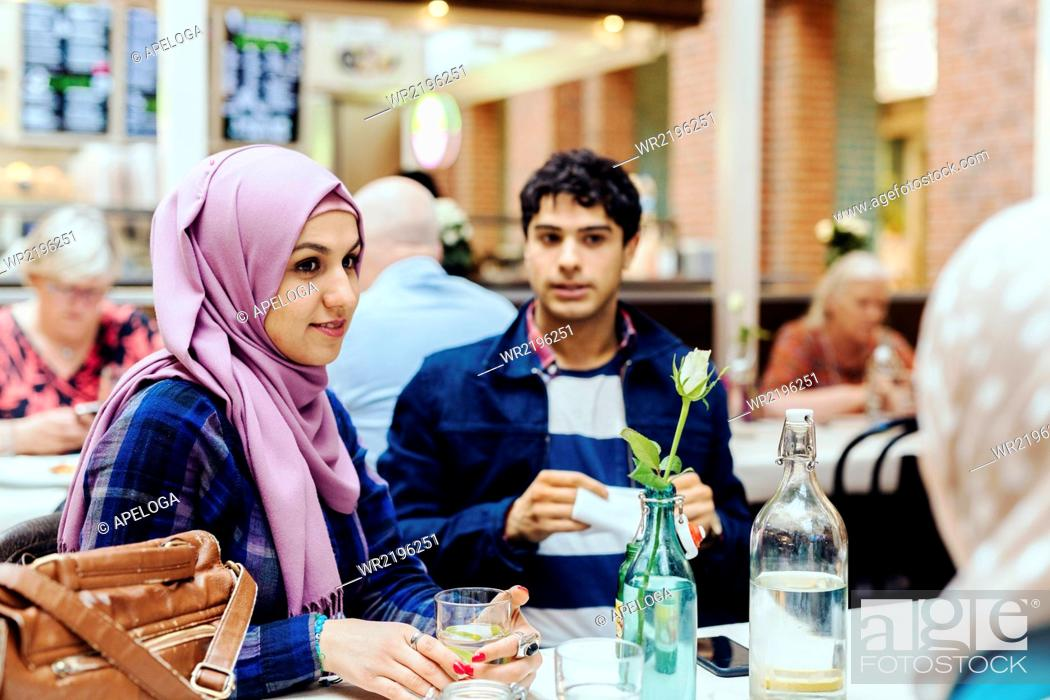 Stock Photo: Woman sitting with friends at table in railroad station cafe.