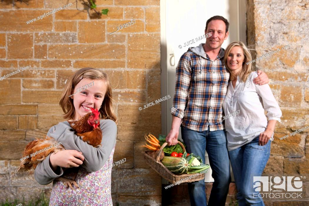 Stock Photo: Girl holding a chicken, parents holding basket of vegetables.