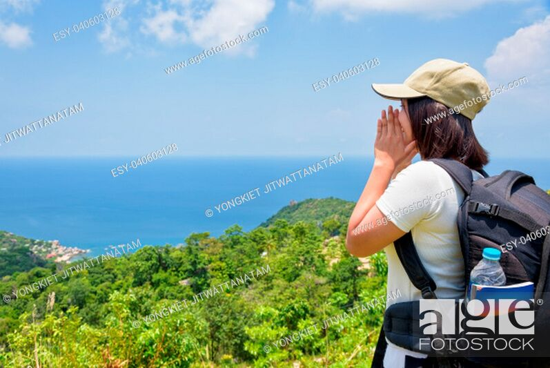Imagen: Women tourist with a backpack wear cap raise hand at the mouth yelling and beautiful nature landscape blue sea and sky from high scenic viewpoint at Koh Tao.