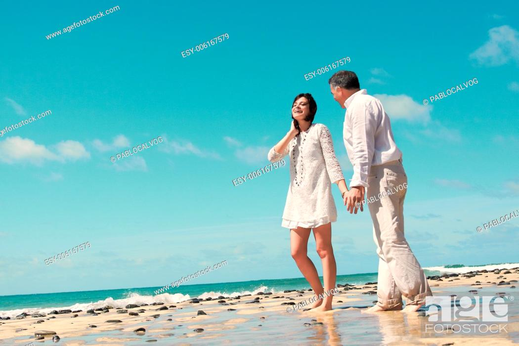 Stock Photo: couple walking, talking and laughing in the sea coast.