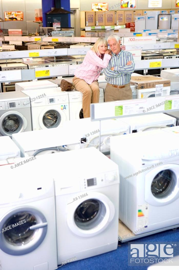 Stock Photo: Mature couple shopping for appliances, woman embracing man with arms crossed.