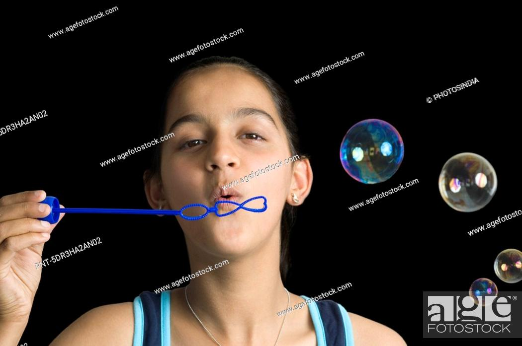 Stock Photo: Teenage girl blowing bubbles with a bubble wand.