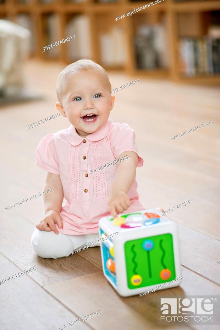 Photo de stock: Baby girl playing with a musical block toy.
