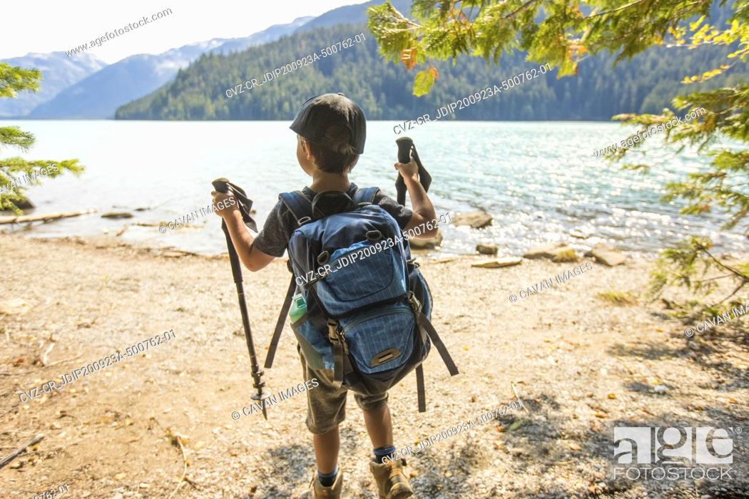Photo de stock: Rear view of young boy hiking by lake with backpack, hiking poles.