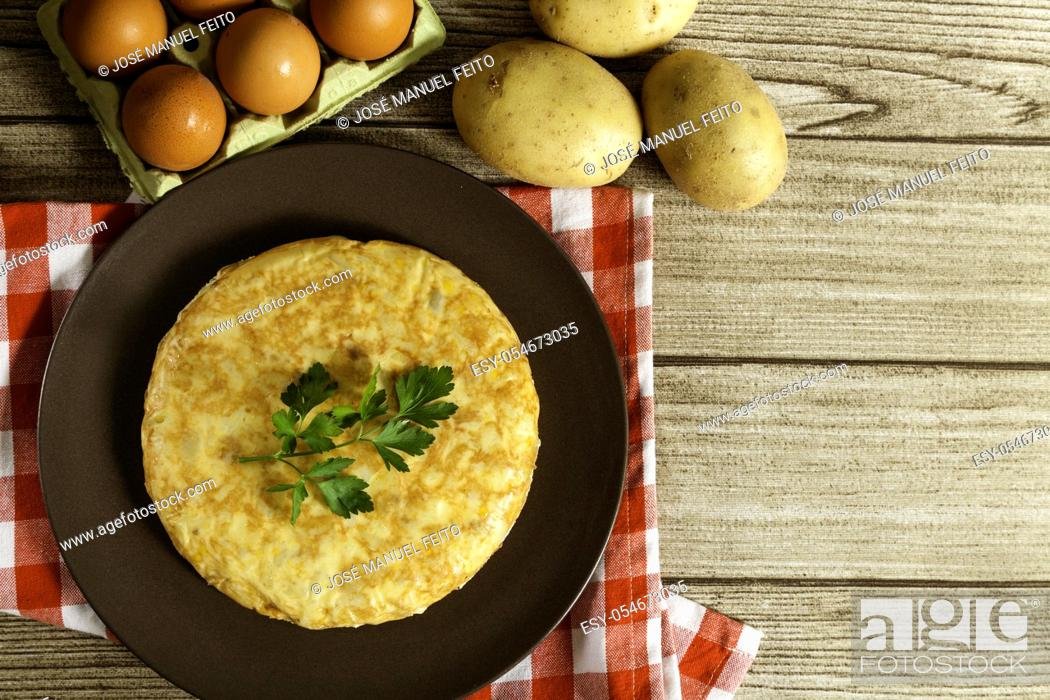 Stock Photo: Spanish omelette in a plate, potatoes and eggs on wooden table from above. Top view.