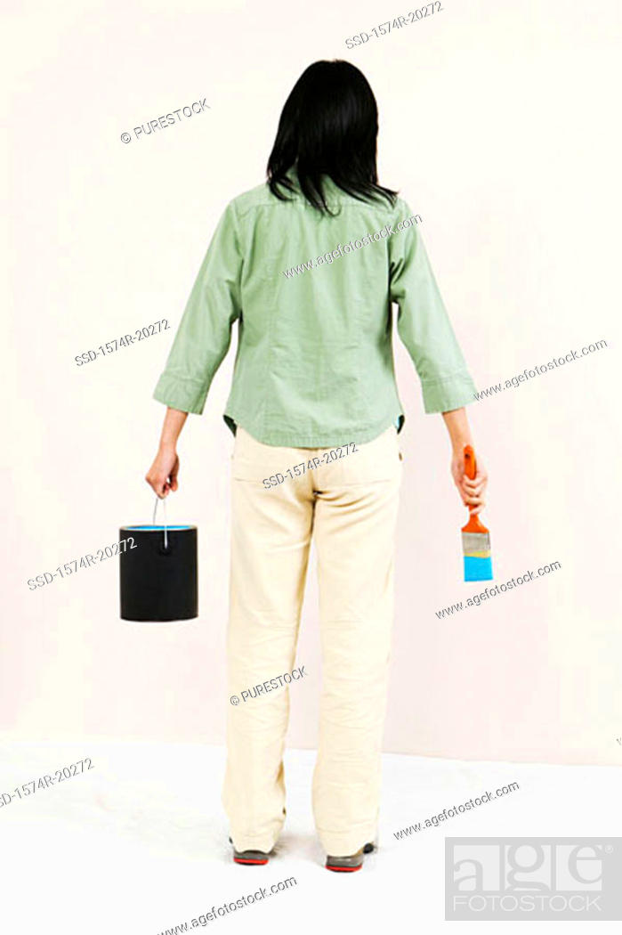 Stock Photo: Rear view of a woman holding a paint can and a paintbrush.