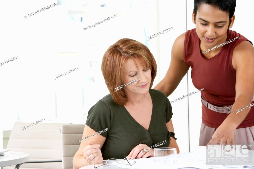 Stock Photo: Two women conferring at office desk.