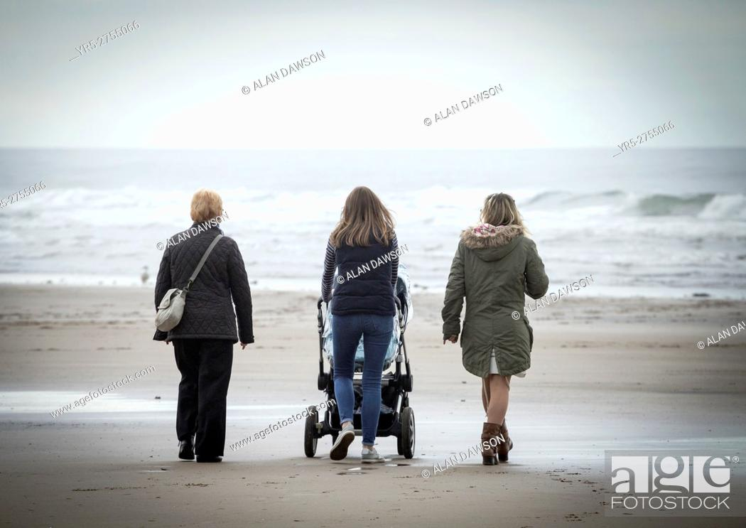 Stock Photo: Woman walking on beach with baby in pushchair on a cold and grey day at Saltburn by the Sea, North Yorkshire, England. United Kingdom.