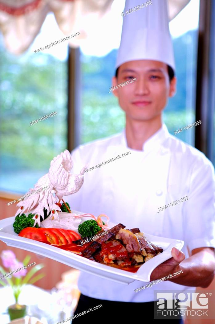 Stock Photo: Chef holding a serving dish and looking at the camera.