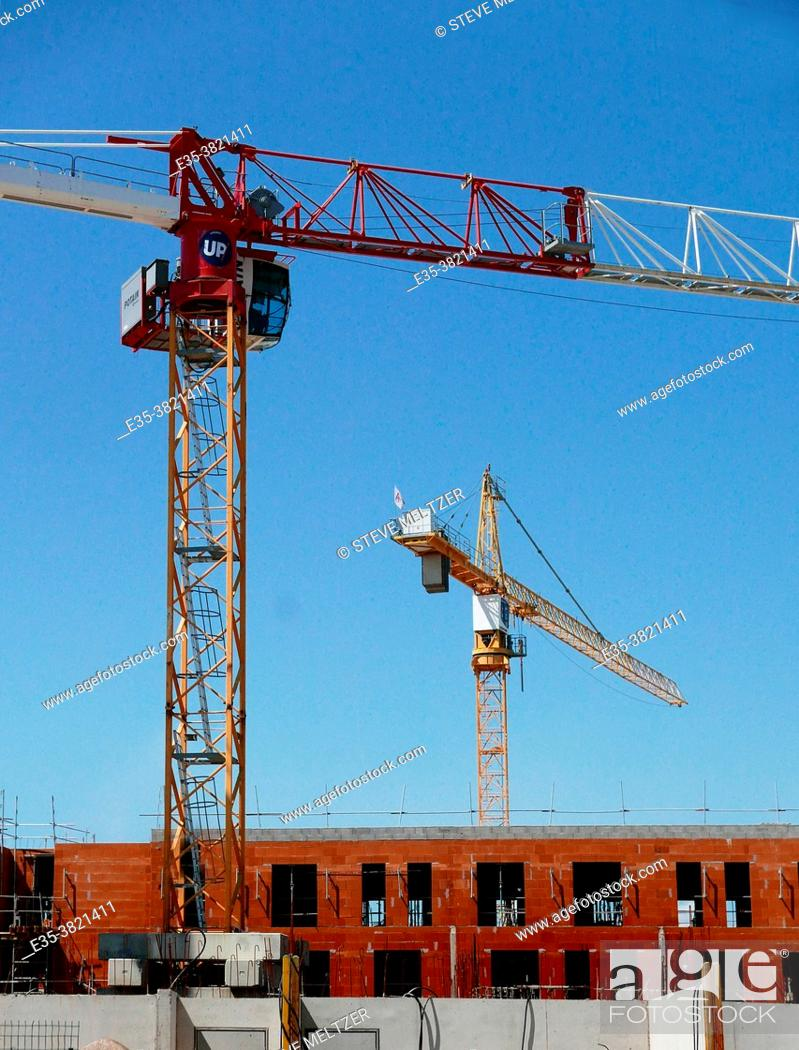 Stock Photo: A construction worker in the distance checks new work done on a building housing.