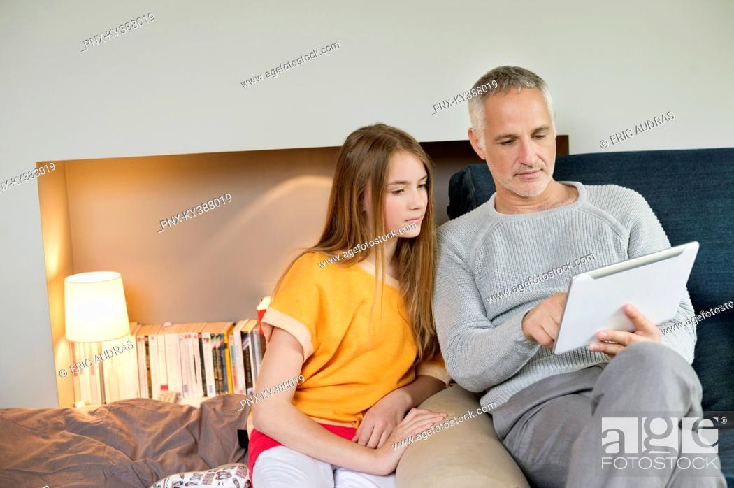 Stock Photo: Man using a digital tablet with his daughter at home.