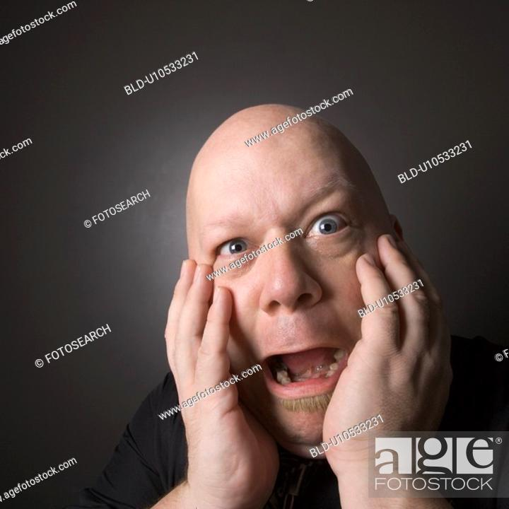 Stock Photo: Bald man with hands to face making scared facial expression.