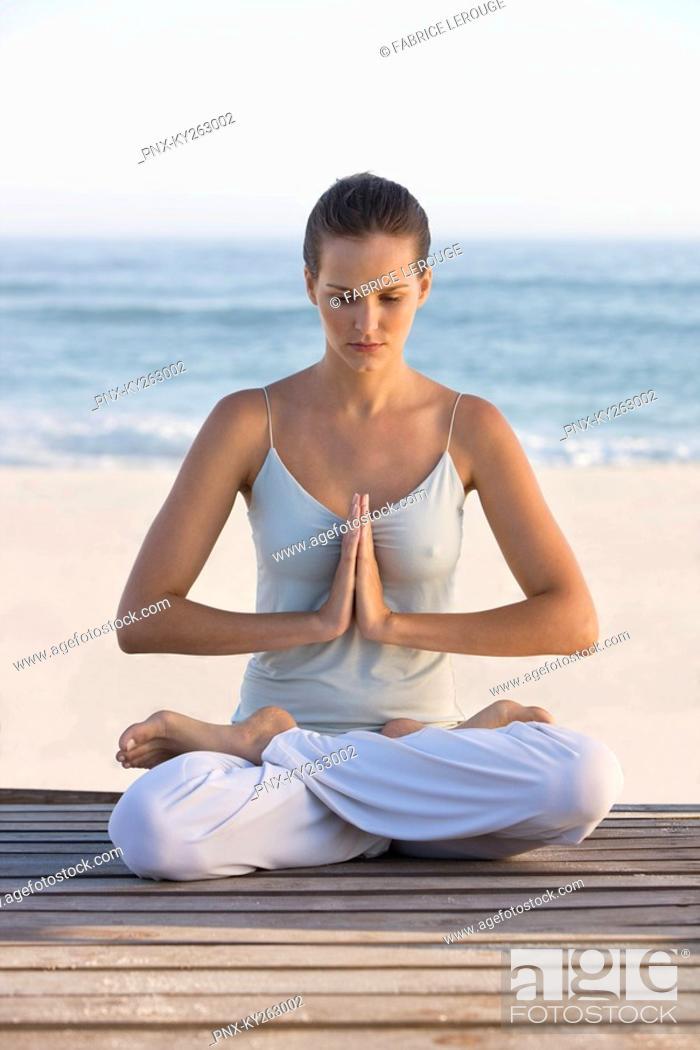 Stock Photo: Woman meditating on a boardwalk.
