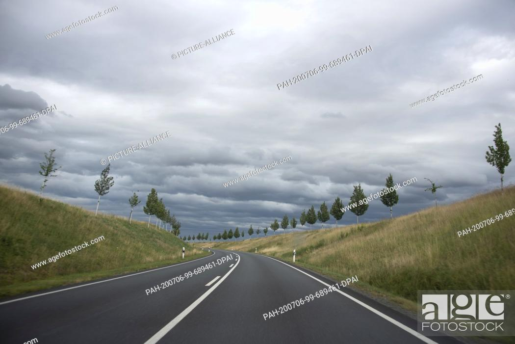 Stock Photo: 05 July 2020, Saxony-Anhalt, Gernrode: Dark clouds hang over a country road near Gernrode in the Harz Mountains. To the left and right of the road small trees.