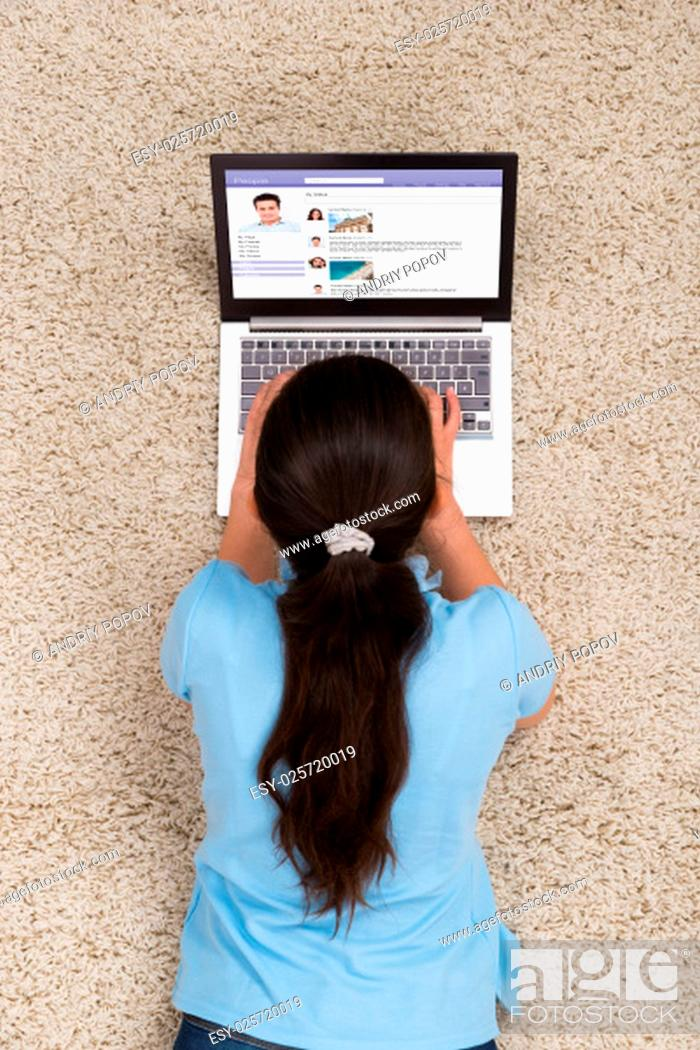 Stock Photo: Woman With Laptop Surfing On Social Networking Site While Lying On Carpet At Home.